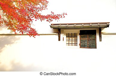 Old japanese warehouse window and maple tree in autumn color