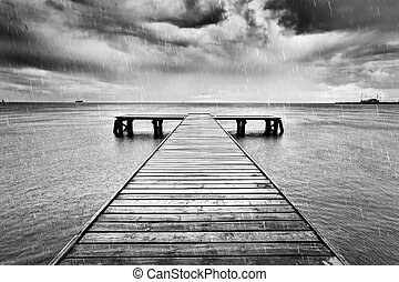 Old jetty, pier on the sea. Black and white, rain.