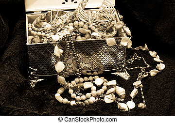 Black and white image of a silver jewellry box with jewellry on black fur