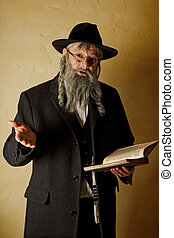 Old jewish man with grey beard holding a book