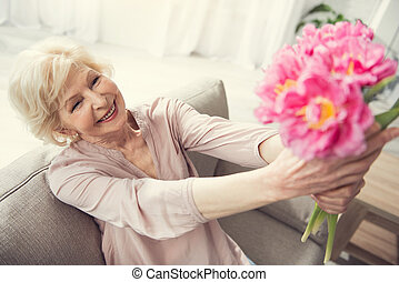 Old joyful woman sitting with flowers