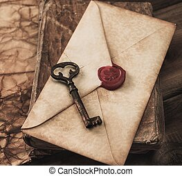 Old key and envelope on a vintage book
