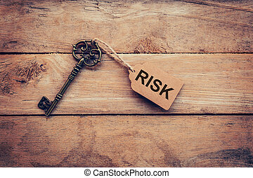 Old key and tag lable RISK for on wooden for business concept.
