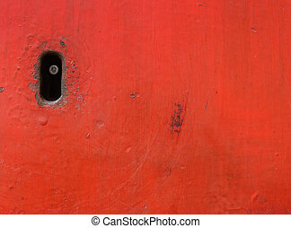 old key-hole embedded in worn red metal surface