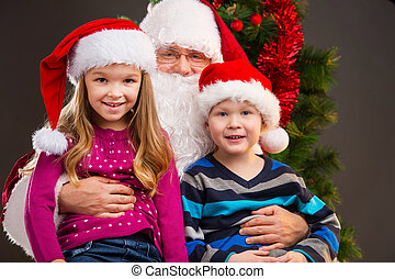 Old kind Santa Claus holding two little kids on his knees. Smiling and looking at camera with Christmas tree on background
