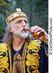 Old king drinking from the goblet - Portrait of old king...