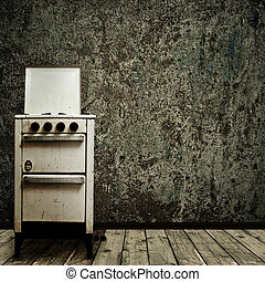 old kitchen - old gas stove over the grunge wall background