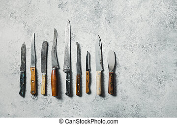 Old knifes on a grey background.