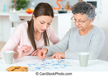 Old lady doing a jigsaw puzzle