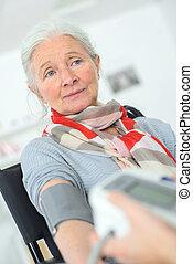 Old lady having her blood pressure taken
