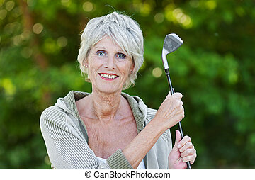 Old lady holding the golf stick - Happy old lady holding the...