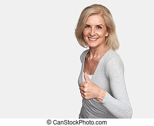 Old lady making thumb up sign - Senior woman smiling. ...