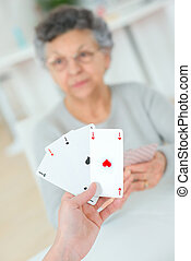 Old lady playing a card game