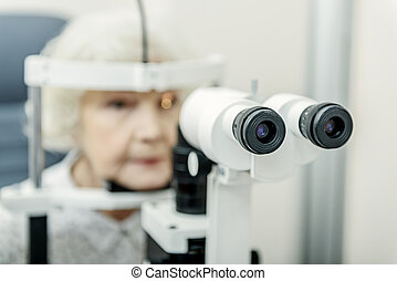Old lady sitting near optical apparatus