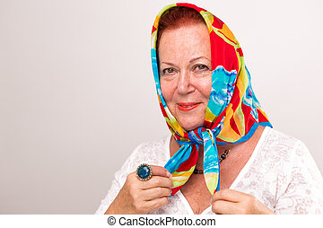 Old lady giving a happy satisfied look in her colorful headscarf