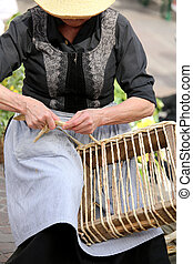 old lady with straw Hat creates a bag