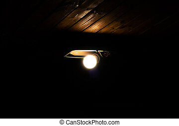 Old lamp on a wooden ceiling in the dark