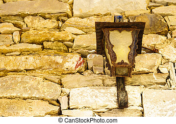 Old lamp on brown stone brick wall