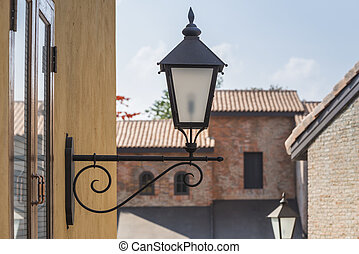 old lamp on the wall with vintage building background