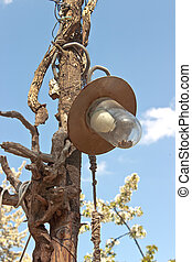 Old lamp on wooden post over blue sky
