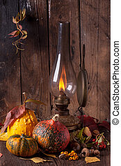 Old lamp with pumpkins, acorns and leaves