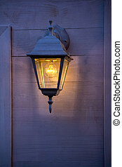 Old lantern burning on the wooden walls