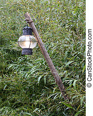 Old lantern hanging on a wooden pole