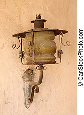 Old lantern on adobe wall