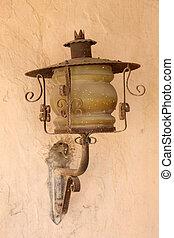 Old lantern on adobe wall