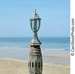 Old lantern on sea beach