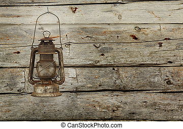 Old lantern hanging on a wooden barn wall