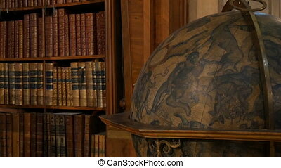 Old large vintage antique globe. Beautiful vintage old bookshelves with nameless books. Interior of the Austrian National Library with a number of old vintage books on the shelves