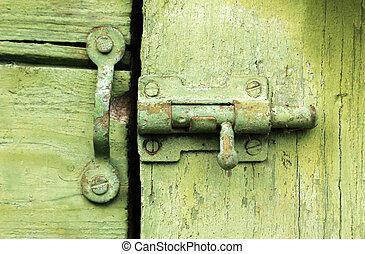 Old latch on green wooden door.