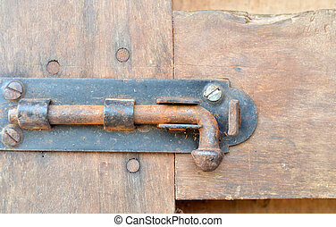 Old latch with padlock on doors