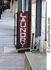 old laundry sign - old red and white laundry sign outside...