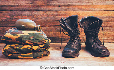 old leather black men boots ankle boots, military uniforms and a flask of water on wooden background front view closeup