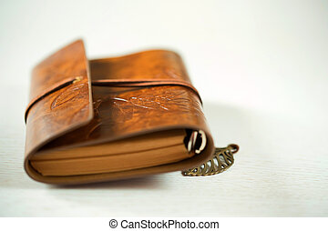 Old leather book on wood background