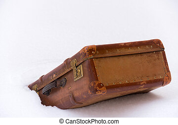 Old leather brown suitcase in the snow