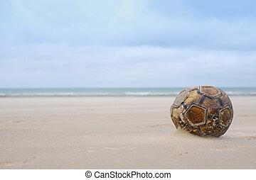Old leather football soccer ball sits on sand beach