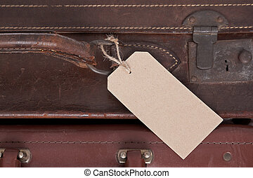 Photo of a blank baggage label on an old brown leather suitcase.
