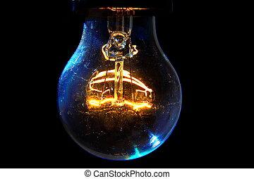 Old light bulb glowing in dark