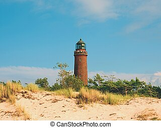 Old lighthouse at Prerow above dunes and pine tree before sunset.