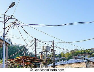 Old lighting post with many electric supply wires or cables for telephone communication