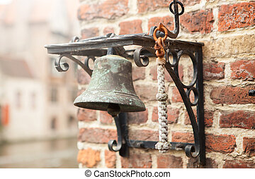 Old little bell on brick wall