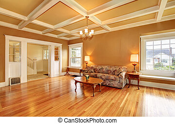 Living room with a coffered ceiling and hardwood floor. Furnished with an antique sofa, coffee table. View of the hallway