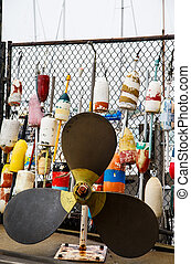 Old lobster buoys hanging on a chain link fence at a harbor with a boat's propeller