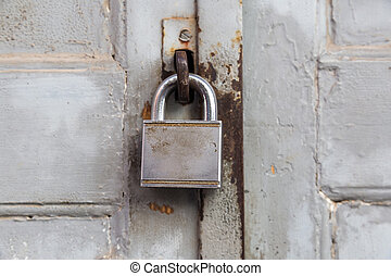 Old lock on wooden grungy painted door closeup.