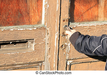 Old locked door - a hand trying to open an old locked door