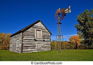 Old log cabin and wind vane - Old preserved log cabin with a...
