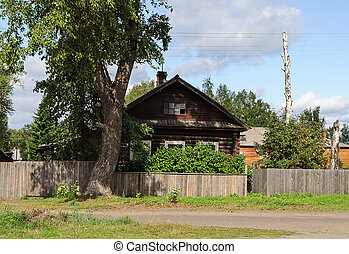 Old log house with a big tree in front - Old log house with ...